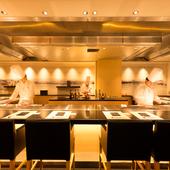 和モダンの広々とした空間で、料理人のパフォーマンスを楽しむ