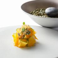 花びらのような一皿は剣先烏賊の炙り、南瓜のムース、鉄南瓜のサラダ。ミモレットとパッションフルーツのソースがコクと香りを高める。別皿のイカスミの最中は、南瓜のピューレとイカスミのラグーを合わせた餡入り。