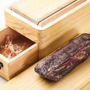 生ハムよりもっと旨みのあるものを作りたいと思い、日本の旨みの基である鰹節をヒントに作ったオリジナルの仔牛節。ほかにも、鶏や鴨、イノシシやシカの削り節を作り、その肉の料理にコクと旨みをプラスしています。