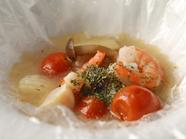 透明フィルムの中に包まれ、より深い旨みとコクが凝縮される『本日の特選魚介と野菜の蒸焼き』