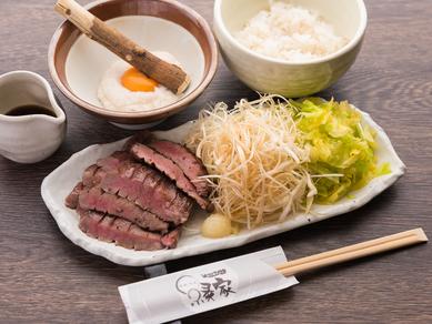 添えてある野菜と一緒にタンを食う『名物!厚切り牛タン焼き(麦めしとろろセット)』