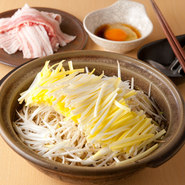 厳選食材の贅沢な旨みを堪能。冷凍していない生の豚肉に、岡山県から直接入荷した希少な「黄ニラ」をたっぷり乗せた贅沢な一品です。長ねぎの旨みとカツオと昆布の旨みが合わさり、旨みと幸せ気分を運んでくれます。