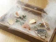 カマンベールチーズ・卵・ベーコン・〆鯖・明太子・いぶりがっこの6種類を桜チップで香りつけした燻製の盛り合わせ。煙の中から現れる斬新な演出に、思わず歓声が上がります。
