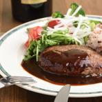 黒毛和牛と国産豚の合挽きミンチを特別な比率で配合したシェフ至高の逸品です。10年以上作り人気の定番メニューです。地元野菜のサラダ、十六穀米orバゲット付