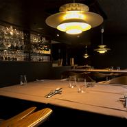 照明がテーブルをやさしく照らす全16席の小さな店。それぞれのテーブルで、美味しい一皿やワインとの出会いがあり、満足の微笑みやゆったりした会話が交わされています。
