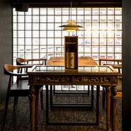 凝ったつくりのガラス天板のテーブル、その上に飾られた古びたボトル。ヴィンテージ感のあるものを設えることで、大人っぽい味わいのある空間を生み出しています。