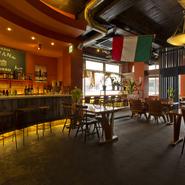 南イタリアをイメージした赤い壁、それに映える観葉植物、高い天井など、オシャレ感満載。ゆったり配置したテーブル席に加え、本格バーの雰囲気の広々としたカウンターも設え。心地いい空気感の中で憩えます。