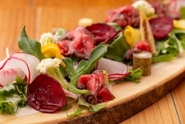 本場の製法でつくられた自家製生ハムを贅沢に盛り付け『今一番美味しい野菜と牛生ハムのシーザーサラダ』