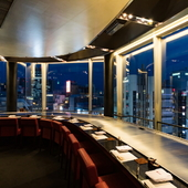 窓の外に広がる夜景を望みながら、ふたりで食事を楽しむ