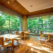 全面ガラス張りの向こうに日本庭園が広がるテーブル席。開放感抜群で、昼は豊かな緑が目に映え、夜は雰囲気たっぷりのくつろぎの空間が広がります。