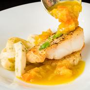 ランチコースの魚料理の一例。白身魚のポワレの下にキノコの焼リゾットを配し、風味と食感をさらにアップ。ゲストの前でサフラン入りソースをかけて供し、リゾットの食感をベストな状態に。五感に響く美味しさです!