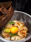 ふっくら炊き上げたお米一粒ひと粒に鶏の旨みが染み渡り、上品でやさしい味わい。底にできたおこげの香ばしさも魅力のひとつです。食事の〆にピッタリな逸品。 ※15~20分程お時間をいただきます。