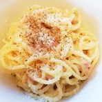 チーズの王様パルミジャーノ・レッジャーノの大きな塊を崩し荒く削りかけます。新鮮なチーズが濃厚なカルボラーナを引き立てます。