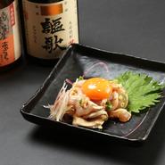 独特な甘みがある九州の醤油を使った自家製のタレと玉子の黄身をからめて食す『知覧どり湯引きユッケ』。海外から訪れるゲストにも人気の一皿は地酒との相性も抜群です。