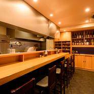 木目の美しいカウンター席は、ゆったりと配置された全7席。店主と会話を楽しみながら料理とお酒を楽しむことができ、串焼や料理を仕上げる様子も見られるので、一人でも楽しい時間を過ごせます。