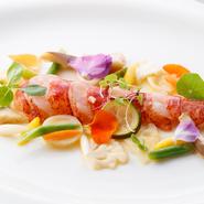 海老の旨味が凝縮されたスペシャリテ。絶妙な火加減でオマール海老を「レア」に焼き上げ、プリップリの食感に仕上げています。季節の旬食材を使ったソースと一緒に食せます。