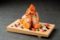 玉子、キュウリを入れた巻き寿司にたっぷりととびっこをまぶし、ネギトロ、キムチをのせスパイシーなチリソースで食べる創作巻き寿司です。