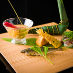 四季折々の演出を凝らした月毎に替わる前菜の盛合せ。「新緑」をイメージし、樹齢200年を超える奈良産吉野杉のプレートに盛られた5月のコースは、『海老の巻粽』『稚鮎導明寺』『畳鰯』などが並びます。