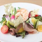 地ものを中心に10数種類の新鮮野菜、海老や生ハムなどをバランスよく盛り込んだサラダは、和テイストのオリジナルドレッシングでいただきます。湯せんした卵の黄身がトッピングされ、目にも鮮やかな一品です。