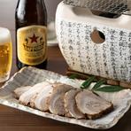炭火の卓上コンロとともに提供され、好みで炙りを加えていただく『炙りチャーシュー』は、丁寧に仕込んだ自家製の味。ビールやハイボール、地酒のつまみにぴったりと、密かに人気を集めている一品です。