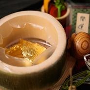 """竹の中に入った料理をゲスト自身が小槌で割って取り出すように、""""自分の手で運を開く""""ような演出で料理を仕上げられています。料理そのものにも金箔が覆われており、高級感と華やかさの化粧を施されています。"""