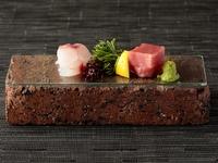 ガラスの器の中には涼しげなジュレを敷き、その上に緑・赤・黄などの彩り豊かにな食材を散らされています。