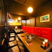 赤いソファー席が目を引く、黒を基調としたスタイリッシュな空間