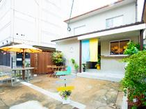 普通住宅のような一軒家に水色と黄色の暖簾と野天傘が目印