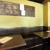 木の椅子とテーブルが落ち着く店内。黒板にはおすすめの日本酒も