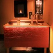 入口を開けた瞬間、1番に目に飛び込んでくる真っ赤なバーカウンター。 前面は日本伝統工法である名栗という技法で削られ、神戸とんぼのテーマカラーでもある朱色が塗られている。 名栗の凸凹が光に照らされ、印象深い色と模様が店内をより一層オシャレに導いている。 バーカウンター奥には、イギリス製暖炉が壁に掛けられており、美しい炎のゆらめきが楽しめる。 見たこともない洗練されたオシャレ空間が神戸とんぼにはあります。