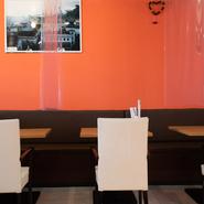お一人様から気軽に足を運ぶことができる【インドマイカレーハウス 荒本店】。オレンジ色の扉を開くと、スタッフが皆優しい笑顔で明るく対応しており、アットホームな空間が広がります。